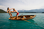Young man pushes girlfriend from a rowing boat into turquoise water, Lake Faak, Carinthia, Austria