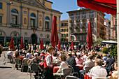 People sitting in a pavement cafea Piazza della Riforma, Lugano, Lake Lugano, Ticino, Switzerland