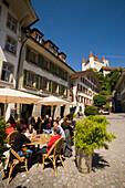 People sitting in pavement cafe of restaurant Ratsstübli, Rathausplatz (town hall square), Castle Thun in background, Thun (largest garrison town of Switzerland), Bernese Oberland (highlands), Canton of Bern, Switzerland