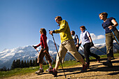 Group of people nordic walking at Bussalp 1800 m, view to Eiger North Face 3970 m, Grindelwald, Bernese Oberland, Canton of Bern, Switzerland