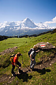 Two people hiking uphill at Bussalp (1800 m), view to Eiger North Face (3970 m), Grindelwald, Bernese Oberland (highlands), Canton of Bern, Switzerland