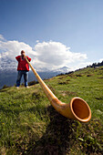 Man playing a alphorn at Bussalp (1800 m), Grindelwald, Bernese Oberland (highlands), Canton of Bern, Switzerland