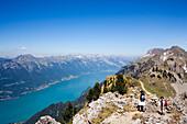 Two hikers enjoying view from Schynige Platte (1967 m) over Lake Brienz, Interlaken, Bernese Oberland (highlands), Canton of Bern, Switzerland