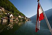 Austrian flag at stern of a ship on Lake Hallstatt, Hallstatt in background, Salzkammergut, Upper Austria, Austria