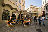 Women passing a pavement cafe, Salzburg, Salzburg, Austria, Since 1996 historic centre of the city part of the UNESCO World Heritage Site
