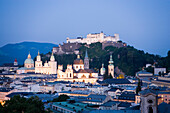 View over Salzburg with Hohensalzburg Fortress, the largest fully preserved fortress in central Europe, Salzburg Cathedral, Franciscan Church, St. Peter's Archabbey and Collegiate Church at night, Salzburg, Austria. Since 1996 the historic centre of the c