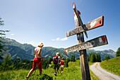 Three hikers walking past a sign post, Bichlalm 1731 m, Grossarl Valley, Salzburg, Austria