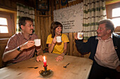 Couple and owner of the Karseggalm drinking coffee, 1603 m, one of the oldest mountain huts in the valley, , Grossarl Valley, Salzburg, Austria