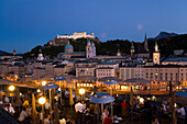 View over illuminated roof deck of restaurant Hotel Stein to old town with Salzburg Cathedral, St. Peter's Archabbey, Franciscan Church, City Hall Tower and  Hohensalzburg Fortress, largest, fully-preserved fortress in central Europe, in the evening, Salz