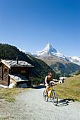 Female mountain biker leaving the mountain village Findeln, Matterhorn, 4478 m, in the background, Zermatt, Valais, Switzerland