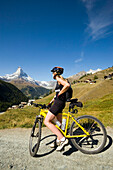 Female mountainbiker looking along the mountain village Findeln to the Matterhorn (4478 m), Zermatt, Valais, Switzerland