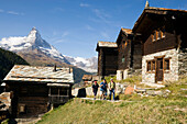 Group of hikers passing the mountain village Findeln, Matterhorn (4478 m) in background, Zermatt, Valais, Switzerland