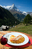 Rösti with fried eggs on a plate and a glass of red wine served in a mountain restaurant, Findeln, Matterhorn (4478 m) in background, Zermatt, Valais, Switzerland