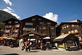 Two snowboarder passing a souvenir shop at Bahnhofplatz, Zermatt village, Zermatt, Valais, Switzerland