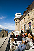 People sitting on terrace of the Kulmhotel restaurant, the highest hotel in the Swiss Alps (3100 m) at Gornergrat, Zermatt, Valais, Switzerland