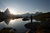 Person watching sunset, east side, Hoernligrat of the Matterhorn, 4478 m, reflected in lake Riffelsee, Zermatt, Valais, Switzerland