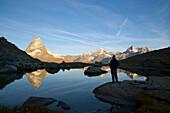 Person watching reflection of the east side (Hörnligrat) of Matterhorn (4478 m) in Riffelsee, Zermatt, Valais, Switzerland