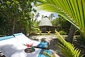 deck chairs and drinks in the garden in front of a traditional Fale, Tonga, South Seas
