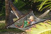Woman with Drink in Hammock, Tonga, South Seas