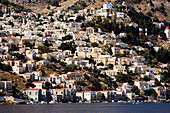 View from Aegean Sea to a sea of houses at mountainside, Symi, Simi Island, Greece