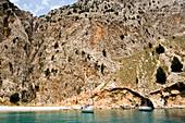 Two sailing boats anchoring near beach in Sisalona Bay, rock face in background, Symi Island, Pedi, Greece