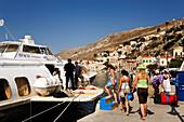 Three young women boarding an excursion boat, Simi, Symi Island, Greece