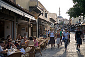 People strolling along shopping street Odos Sokratous, passing a pavement cafe, Rhodes Town, Rhodes, Greece, (Since 1988 part of the UNESCO World Heritage Site)