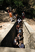 Group of tourists walking through the dark tunnel with ankle high water to reservoir, Epta Piges (Valley of the seven springs), near Colymbia, Rhodes, Greece