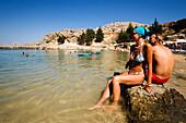 Couple sitting on rocks and talking, Saint Paul's Bay (Agios Pavlos), Lindos, Rhodes, Greece