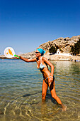 Woman playing beach pingpong, standing in shallow water, Saint Paul's Bay (Agios Pavlos), Lindos, Rhodes, Greece
