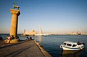 People resting on base of column with deer Elafos at port entrance of Mandraki harbour (translated literally: fold), column with doe Elafia in background, Rhodes Town, Rhodes, Greece