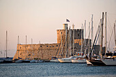 View along anchoring ships at mole with fortress tower Agios Nikolaos in background, Mandraki harbour (translated literally: fold), Rhodes Town, Rhodes, Greece