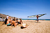 Man carrying a windsurfing sail over beach, group of young woman watching him, Prassionisi Beach, Prassionisi, Rhodes, Greece