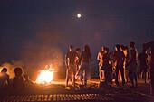 Young people at beach near campfire, sunday party at Sundance Beach Bar, Gennadi beach, Gennadi, Rhodes, Greece