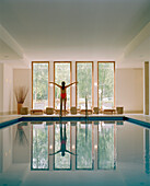 Woman standing with outstreched arms at pool, Hotel Neuklostersee, Nakenstorf, Mecklenburg-Western Pomerania, Germeny, MR, PR