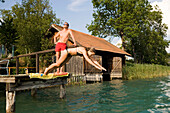 Young woman jumping form a landing stage into Lake Faak, Carinthia, Austria