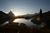 Person watching sunset, east side (Hörnligrat) of Matterhorn (4478 m) reflected in Riffelsee, Zermatt, Valais, Switzerland