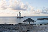 Strandschirm und Segelboot am Malmok Beach, Aruba, ABC-Inseln, Niederländische Antillen, Karibik