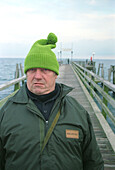 fisherman at the Baltic sea, Germany, portrait, people from germany, german, man with cap, man with pompom hat, pompom hat, green pompon hat, direct view, direct look in the camera, straight look in the camera, grim, a grimmer man, grimmer look, headgear,