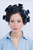 Young woman with curlers in hair, portrait