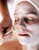 Woman receiving spa facial treatment