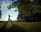 Woman relaxing doing a yoga excercise in the park area of a Wellness Hotel at sunset, near Hameln, Lower Saxony, germany