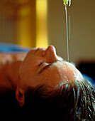Woman enjoying an oil infusion, ayurveda massage, Wellness treatment in a Wellness Hotel, Germany