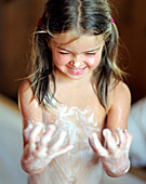 Wellness for children, girl has covered herself with a natural body mixture of honey, oil and cream, Wellness Hotel, Germany