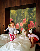 Two girls jumping around on a bed, Hotel Room, Spa Hotel Seehotel Neuklostersee, Mecklenburg - Western Pomerania, Germany