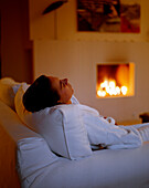 Woman relaxing near an open fire place, relaxation room, Spa Area of Seehotel Neuklostersee, Mecklenburg - Western Pomerania, Germany