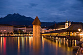 View over the river Reuss with illuminated chapel bridge, the oldest covered bridge in Europe and water tower in the evening with Jesuit Church, the oldest, largest baroque building in Switzerland and Pilatus Summit in the background, Lucerne, Canton Luce