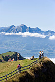 Hikers on Rigi Kulm (1797 m) enjoying the view over Lake Lucerne to Pilatus (2132 m), Rigi Kulm, Canton of Schwyz, Switzerland