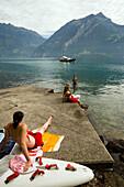 Girls sunbathing on rock, Lake Urnersee, part of Lake Lucerne, Bauen, Canton of Uri, Switzerland