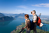 Mature adult couple at Kanzli vantage point on Mount Rigi (1797 m, Queen of the Mountains) looking over Lake Lucerne and Weggis, Mount Bürgenstock and Mount Pilatus (2132 M) in the background, Rigi Kaltbad, Canton of Schwyz, Switzerland